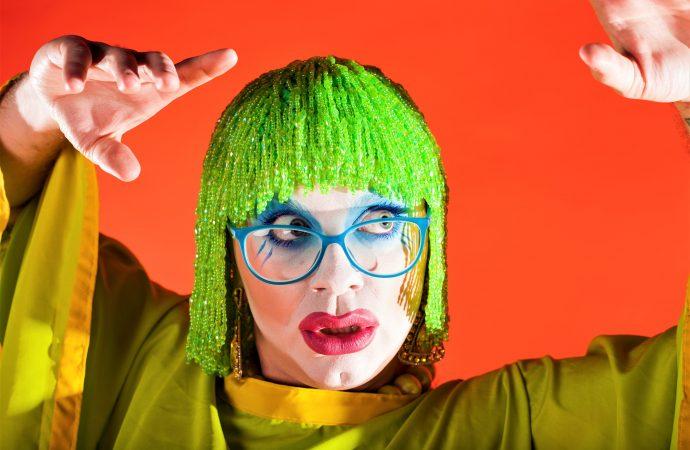 Former FWD artist Ginny Lemon in a green wig against an orange background